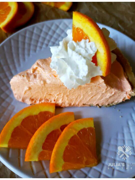 Orange Dreamsicle Chiffon Pie topped with whipped cream and an orange slice garnish on a plate