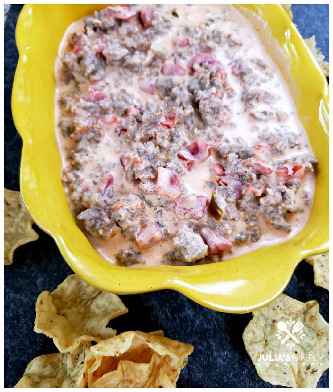 Sausage Dip recipe served in a yellow dish with corn chip scoops