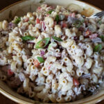 A large serving bowl with creamy tuna macaroni salad garnished with scallions