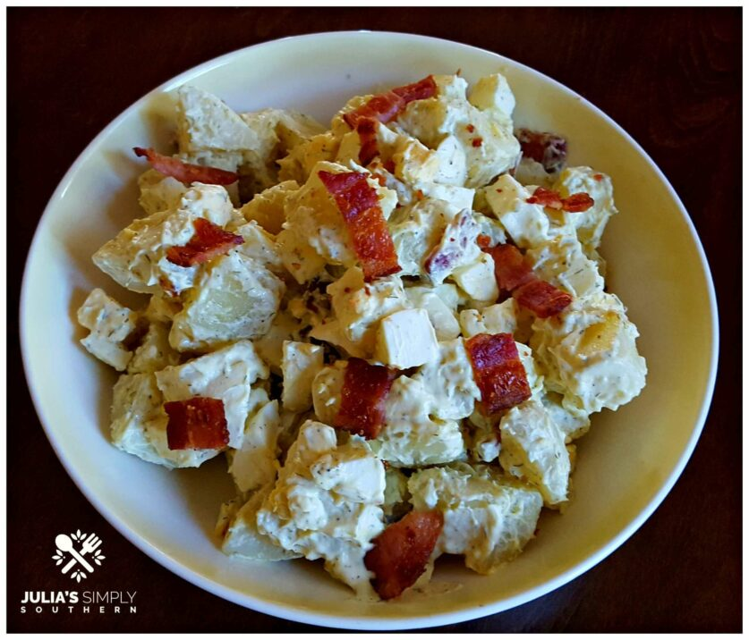 Small batch Southern style potato salad short cut version side dish with bacon in a vintage yellow and white bowl