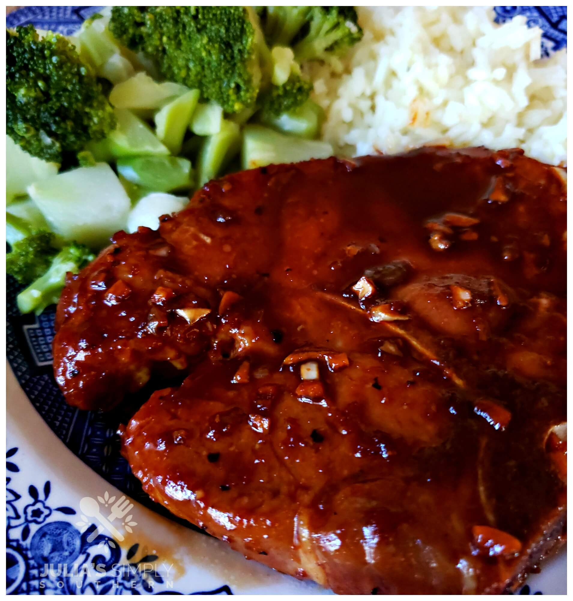Sticky Garlic Pork Chops on a plate with broccoli and rice