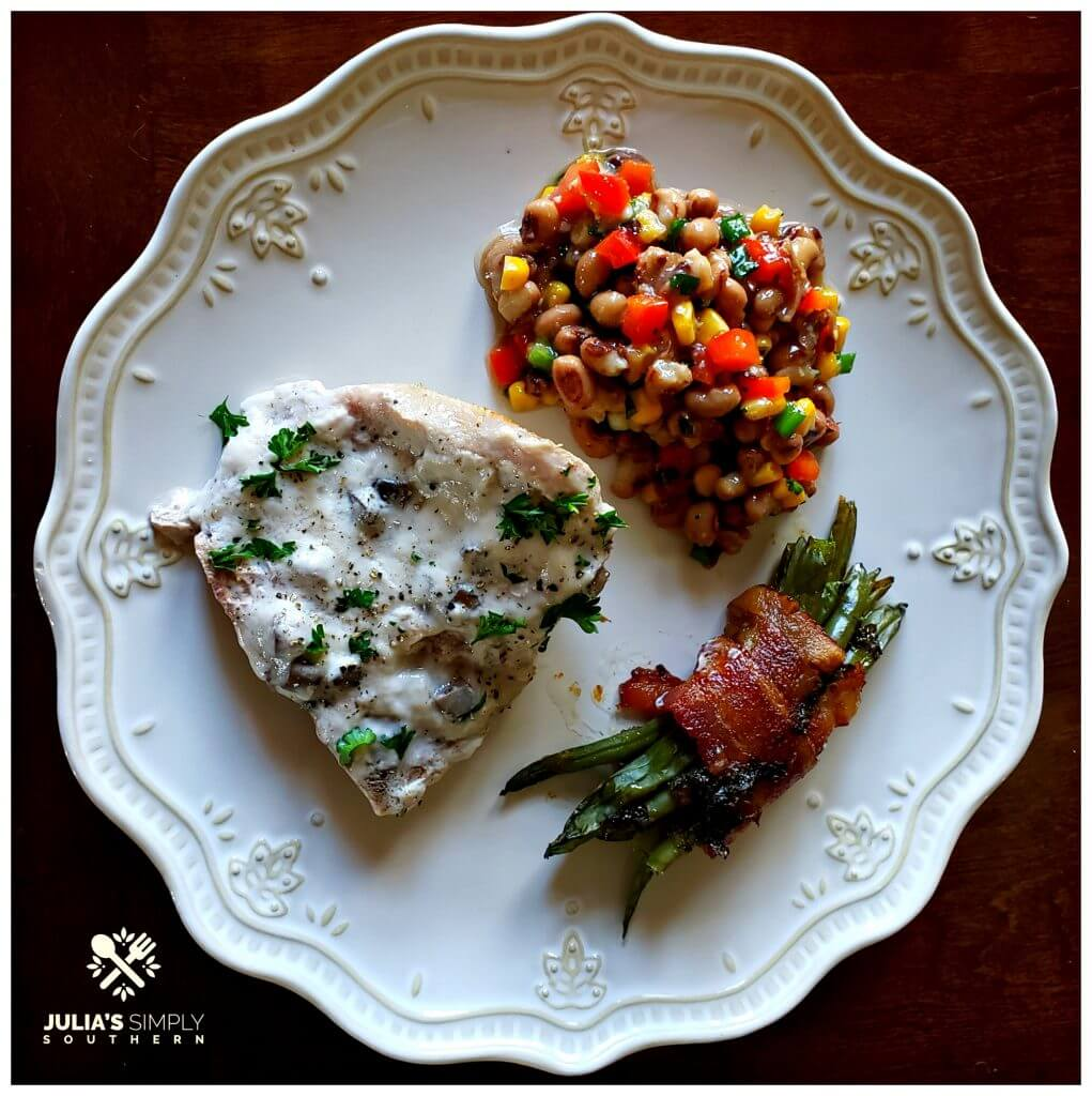Campbell's Cream of Mushroom Pork Chops Recipe baked on a plate with green bean bundles and black eyed pea salad