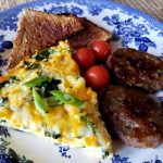 Crustless vegetable quiche recipe on a plate with cherry tomatoes, toasted bread and sausage patties