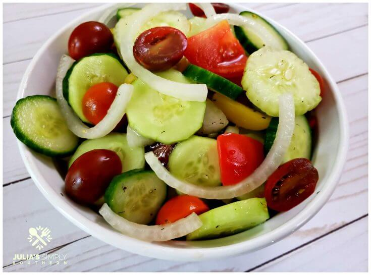 Colorful cucumber salad with tomatoes and onions in a white serving bowl