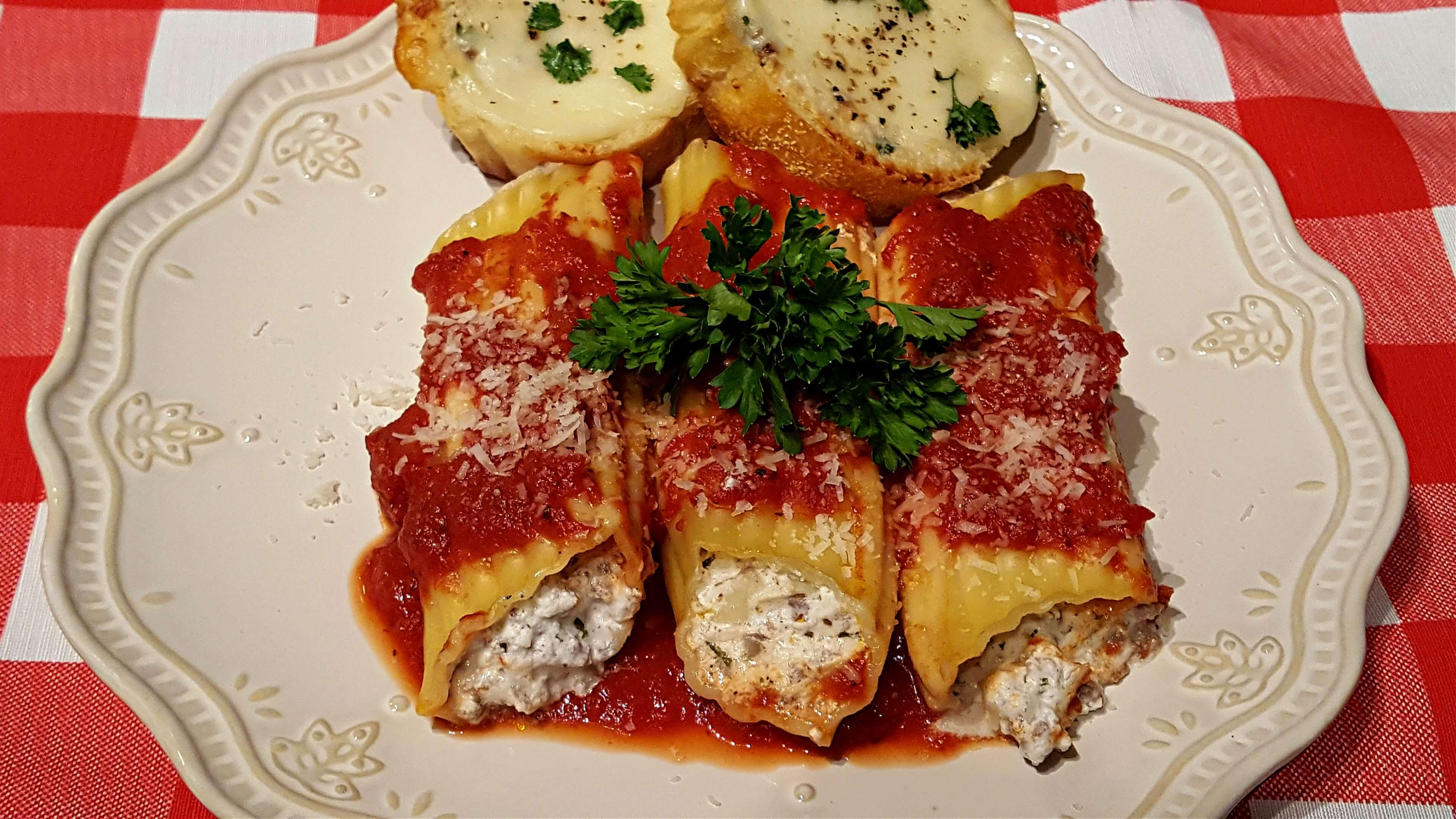 Beef manicotti with red sauce on a plate with a side of garlic cheese toast