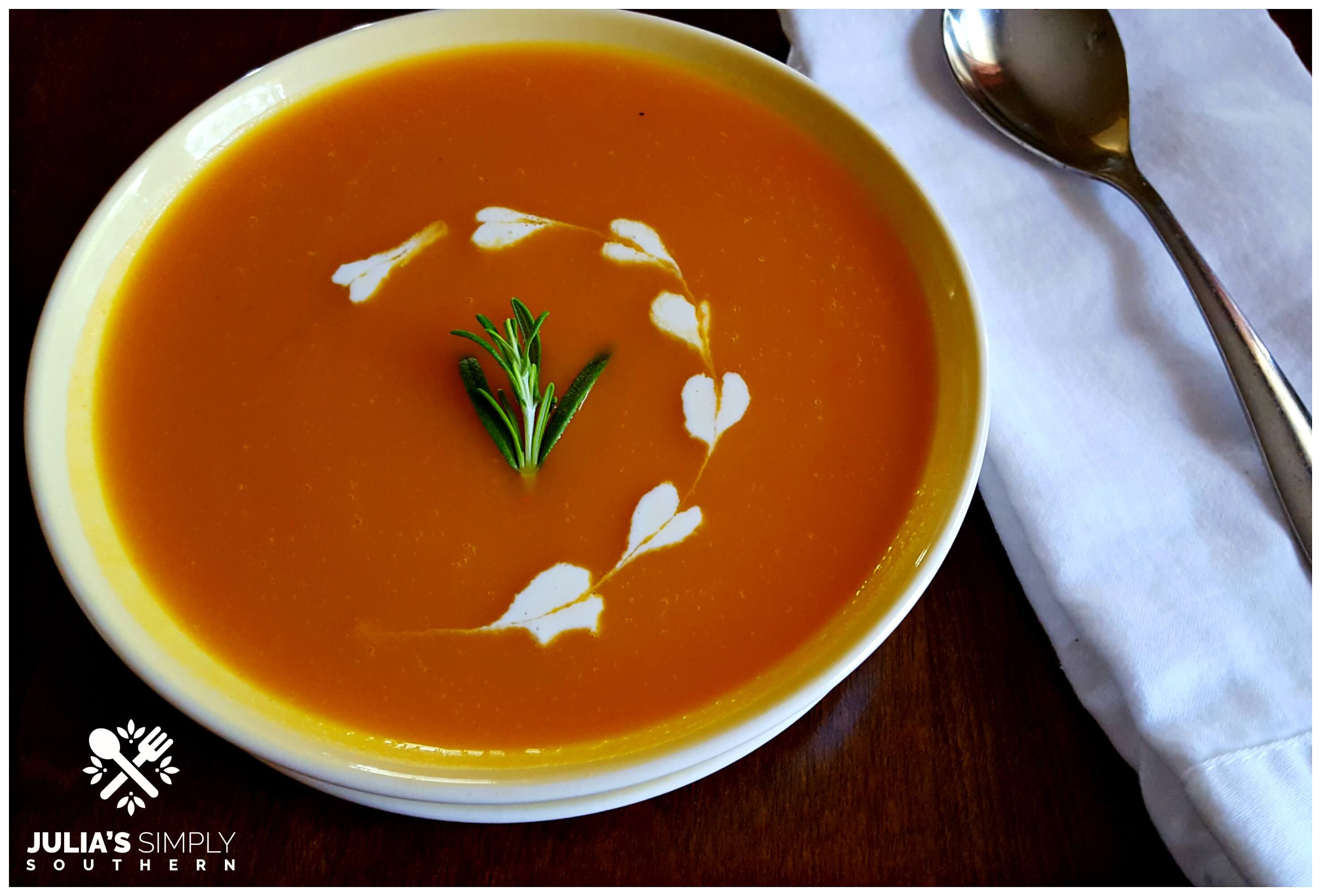 Bowl of the best pumpkin soup recipe with dots of heavy cream hearts and a sprig of Rosemary garnish