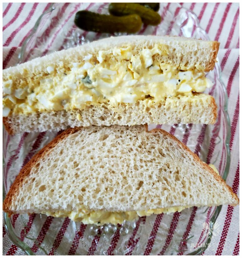 Simple egg salad sandwich recipe on a glass plate on top of a red and white ticking towel