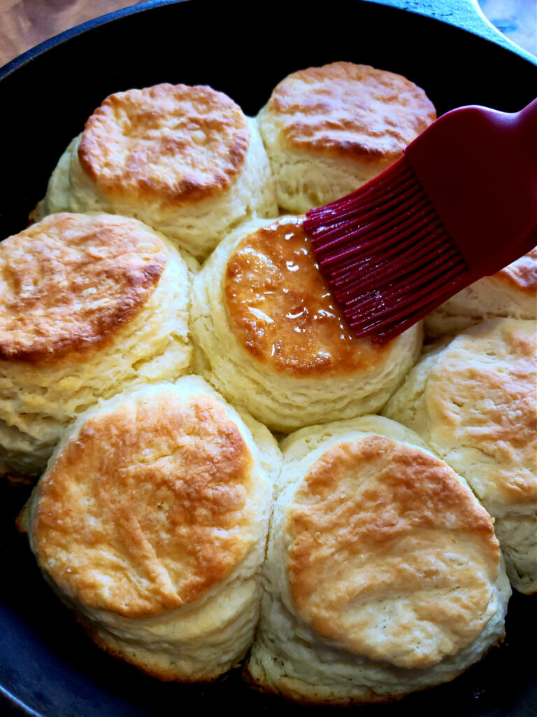 Brushing butter over fresh from the oven scratch made biscuits