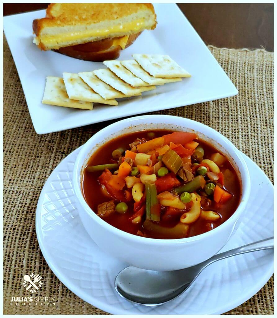 Bowl of homemade V8 Vegetable Soup with crackers and a grilled cheese