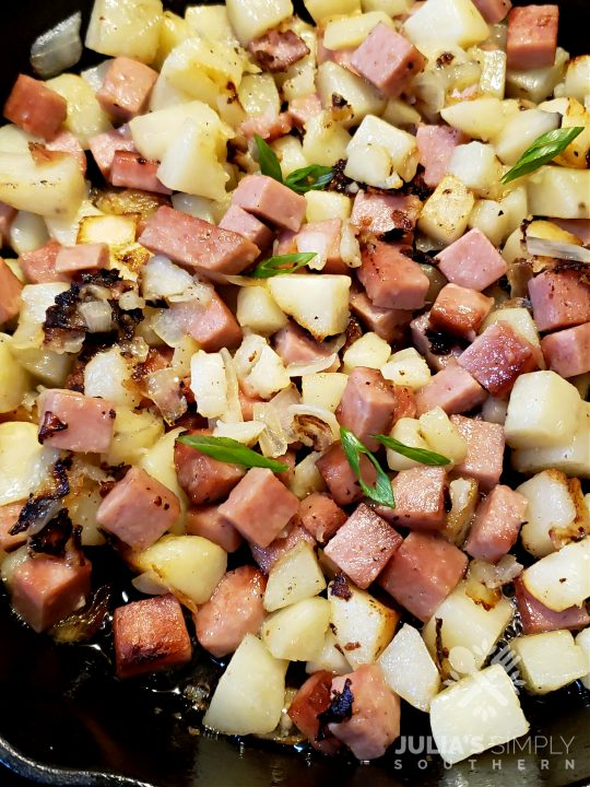 Cast iron skillet with diced potatoes and Spam with onion