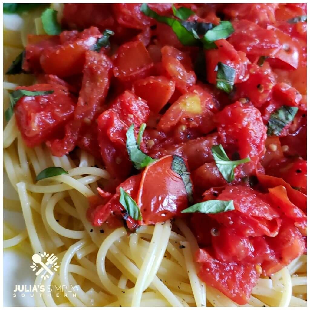 Beautiful red stewed Roma tomatoes on a bed of pasta with fresh basil and olive oil