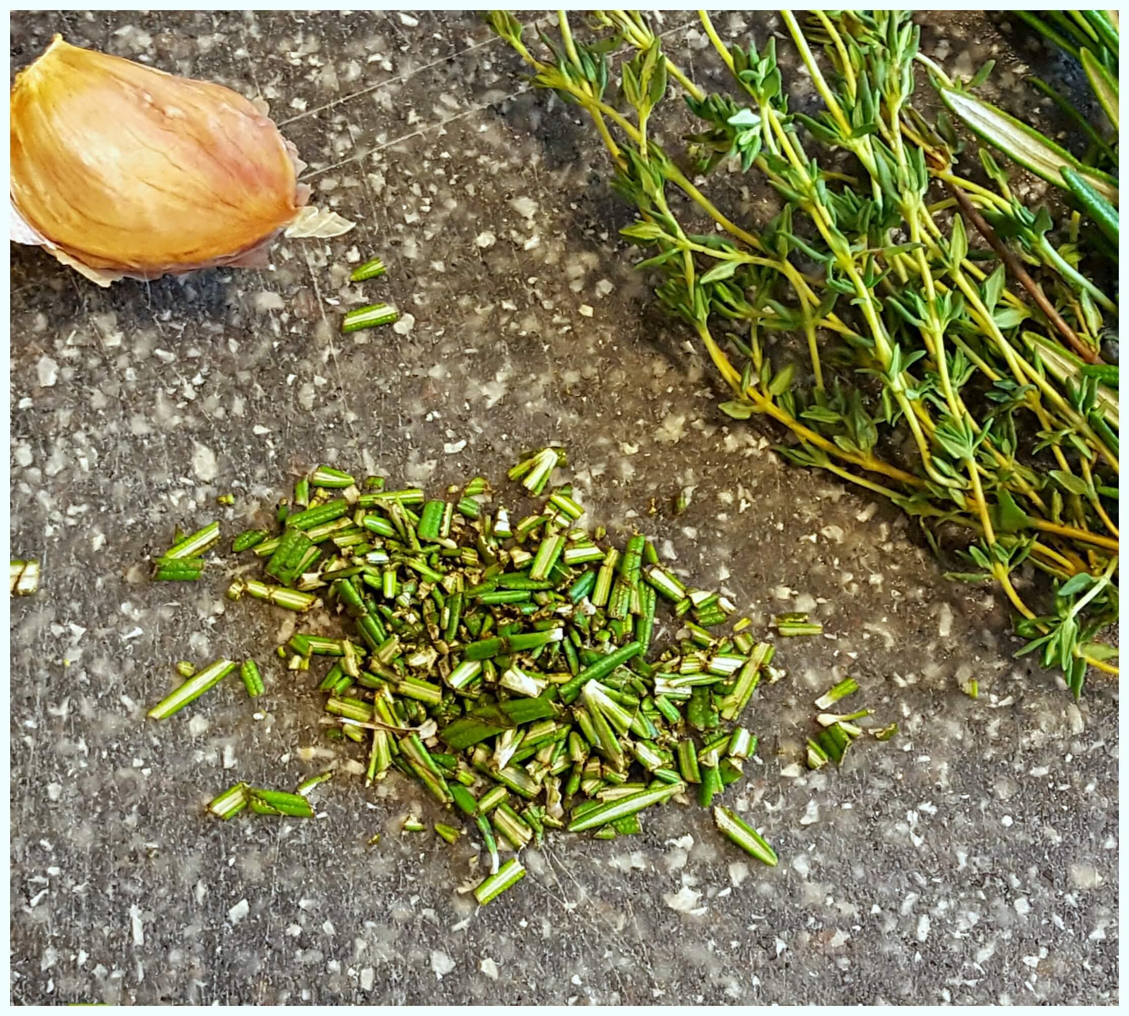 fresh herbs and garlic on a cutting board