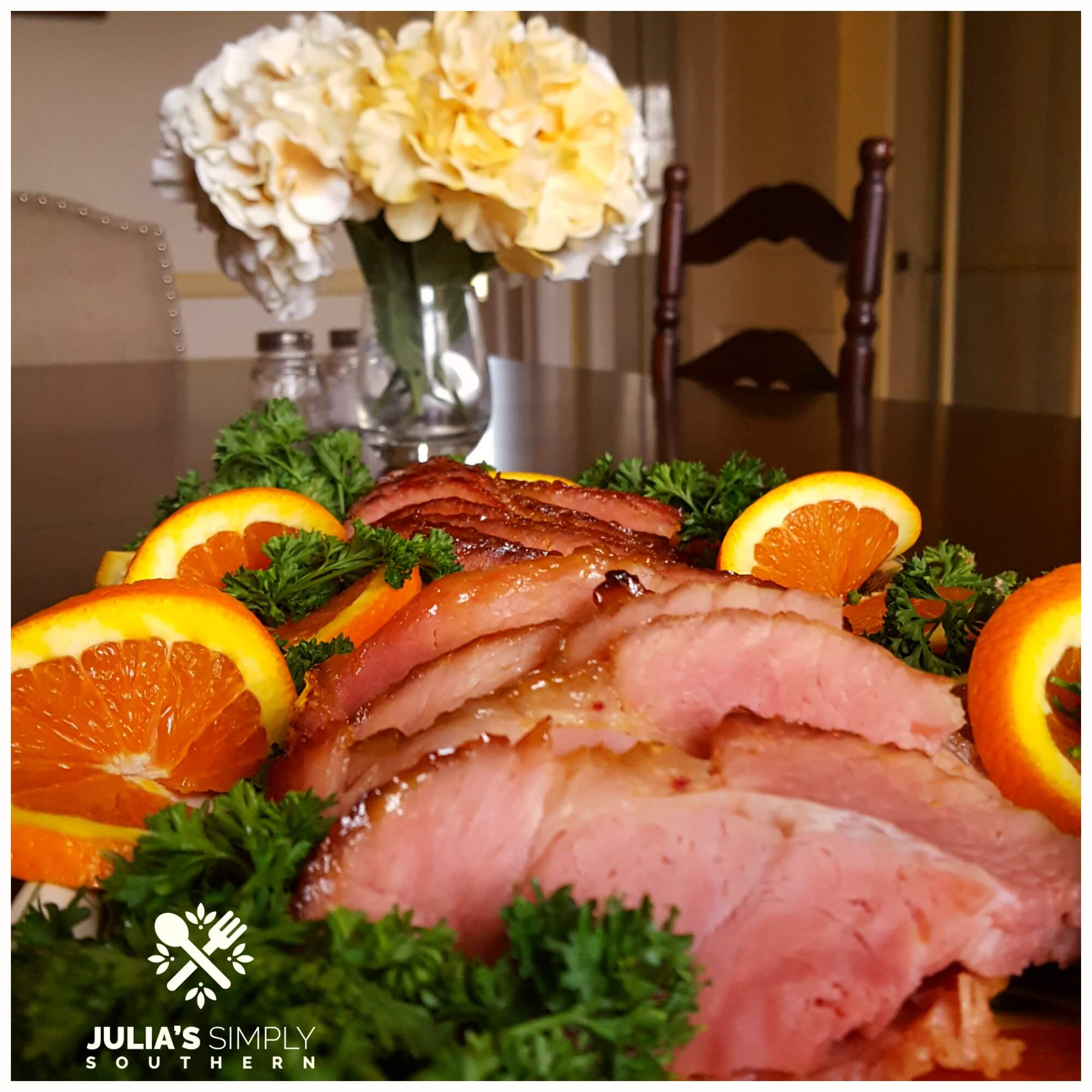 Glazed Ham with a Honey Orange Glaze on a dining table with flowers in the background.