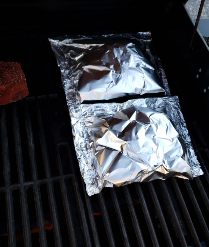 foil packets with broccoli on a gas grill cooking