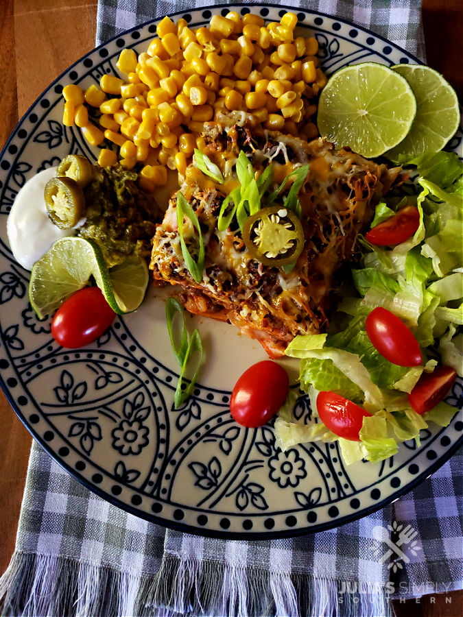 Dinner plate with Mexican casserole and sides with checked towel