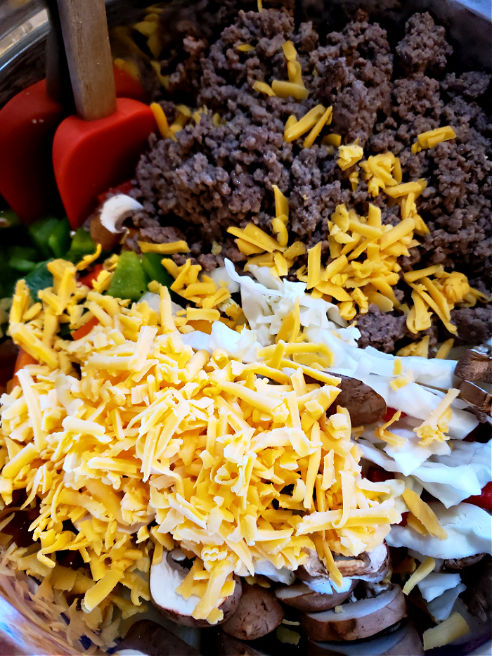Combine cheesy ground beef and cabbage casserole ingredients in a mixing bowl with cream of mushroom soup