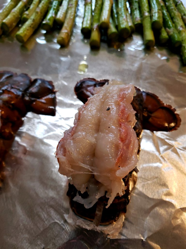 Preparing lobster by butterflying the tail and placing on a baking sheet