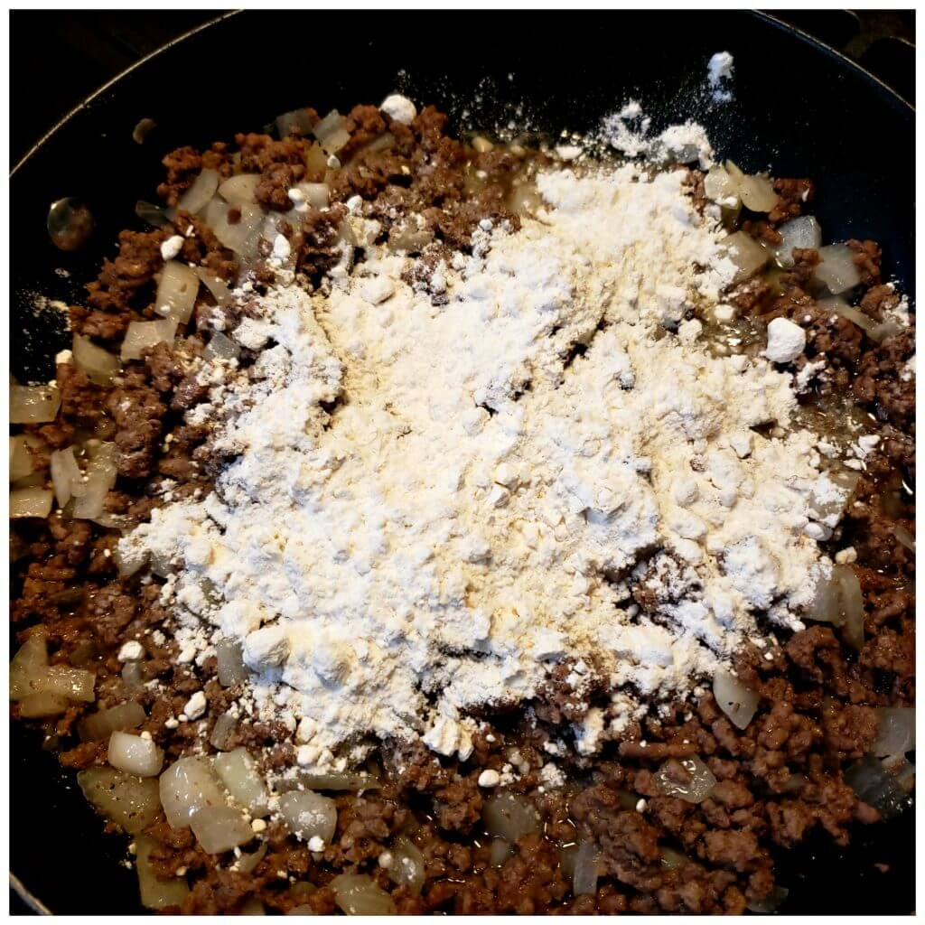 Cooked ground beef in a skillet with flour to make a gravy sauce