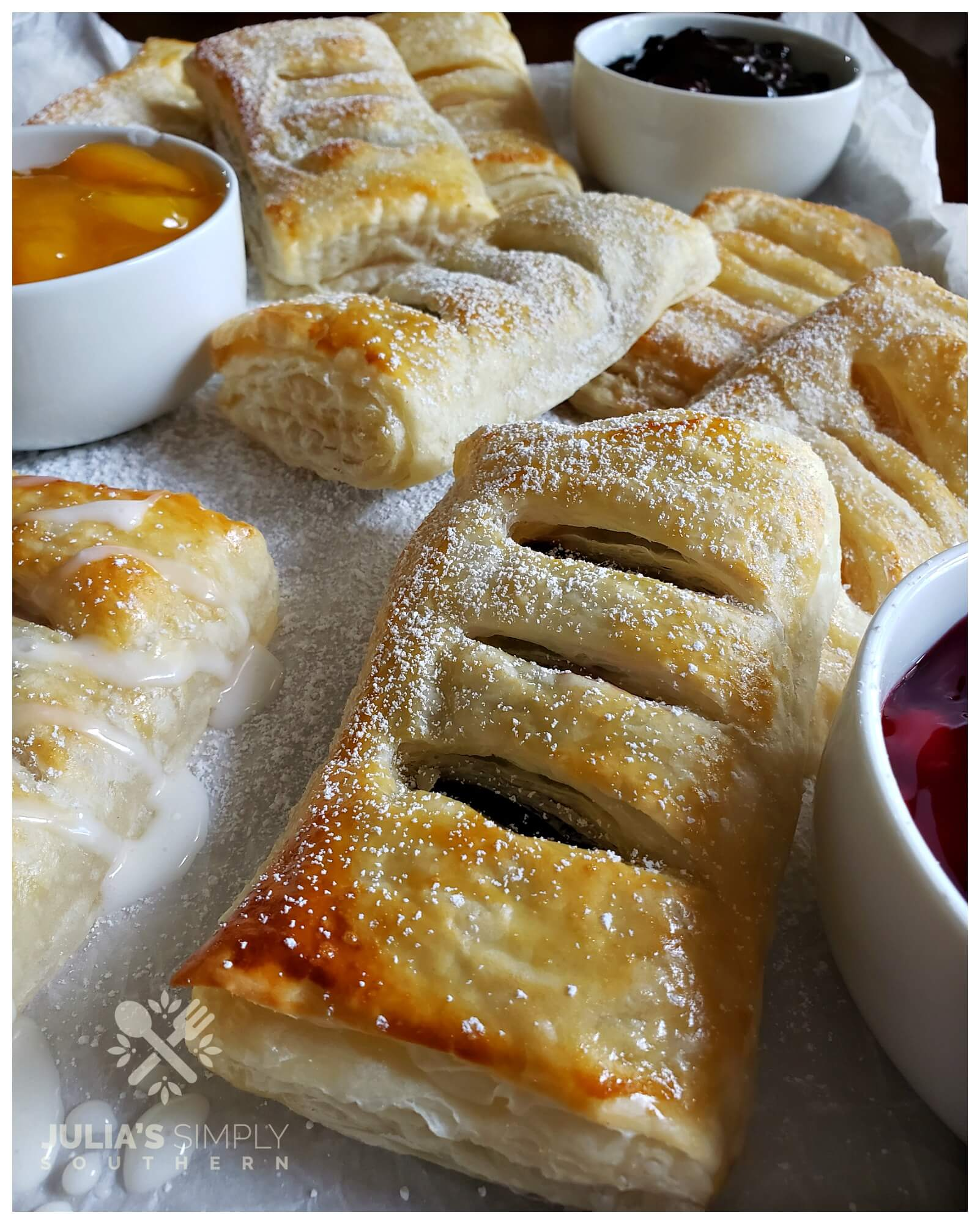Assorted fruit hand pies on a silver baking sheet that has been lined with parchment paper and dusted with powdered sugar.