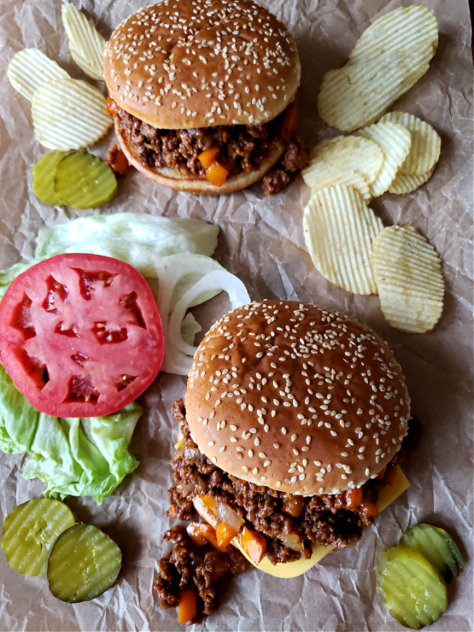 Sloppy Joe sandwiches with topping options served with potato chips. Homemade Sloppy Joes recipe.