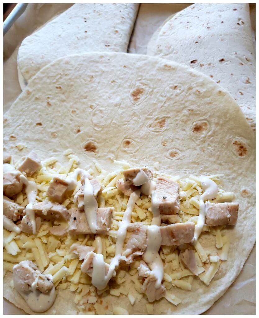 Layering ingredients inside a large flour tortilla before baking