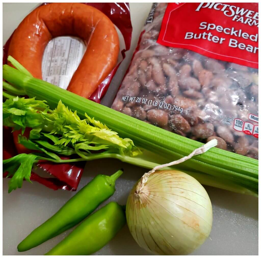 White cutting board with a package of speckled butter beans, vegetables and smoked sausage