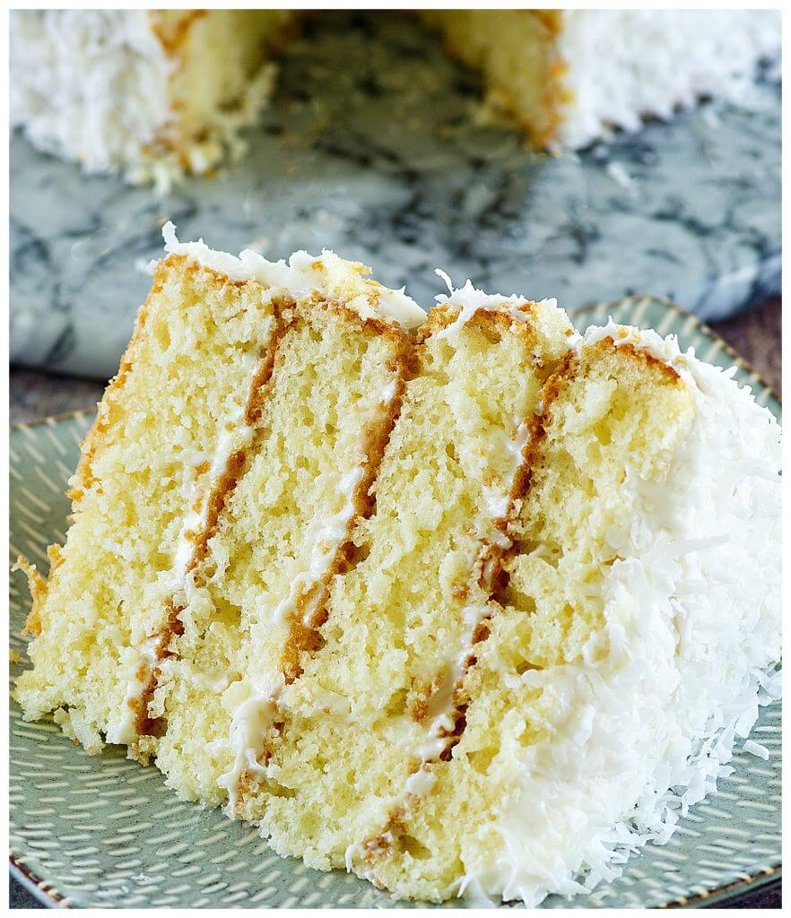 Delicious layered Southern coconut cake recipe with frosting topped with flaked coconut