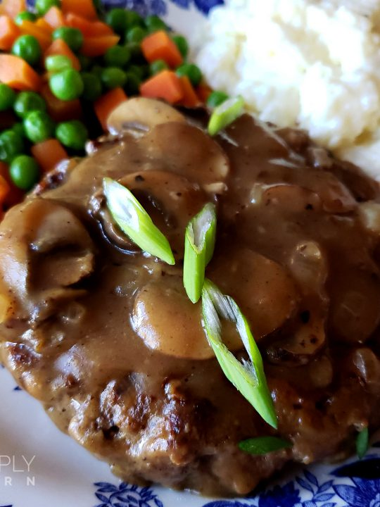 Southern Salisbury Steak Recipe with mushroom gravy served with a side of mashed potatoes and peas and carrots