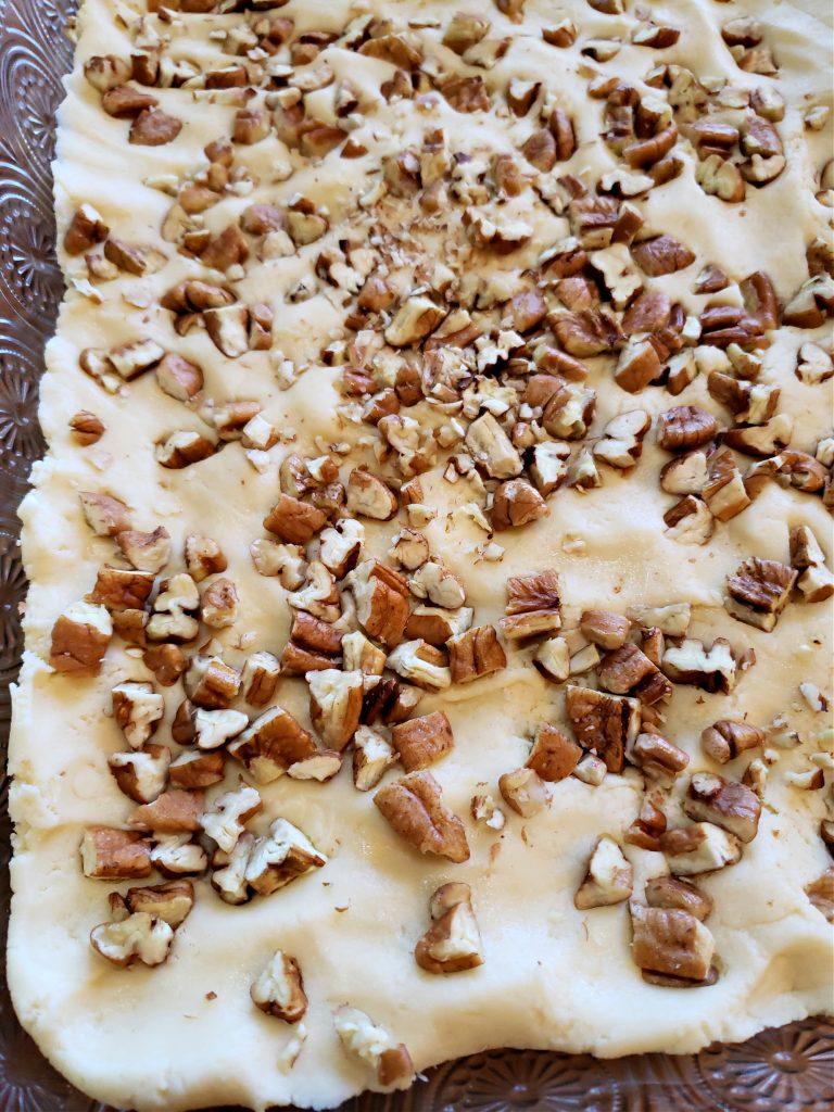 Pressing pecans into goody bar cake dough