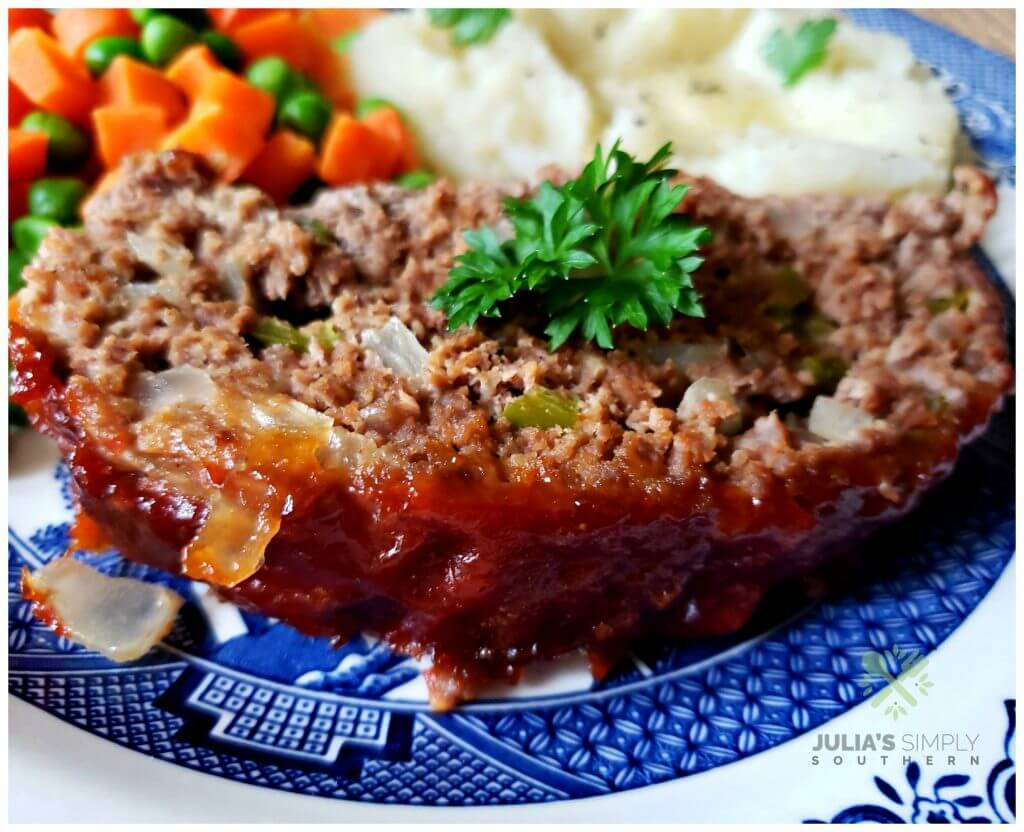 Delicious slice of Southern Style Meatloaf served with mashed potatoes and peas and carrots with a parsley garnish