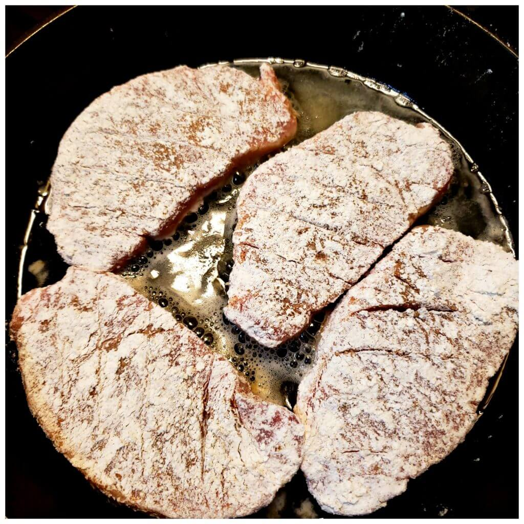 Pork chops seasoned and dredged in flour browning in cooking oil in a cast iron skillet