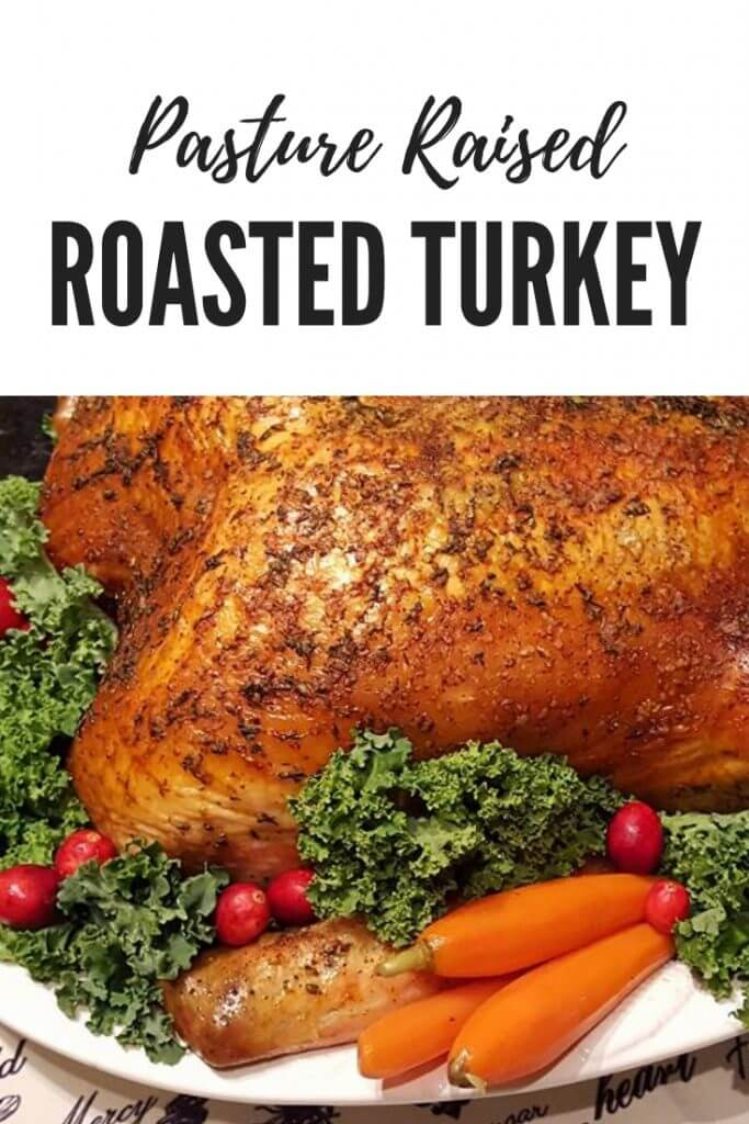 Herb Roasted Turkey on a serving platter garnished with leafy greens, baby carrots and cranberries