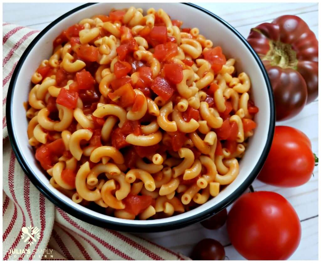 Bowl of classic macaroni with tomatoes surrounded by fresh garden tomatoes and a red ticking towel
