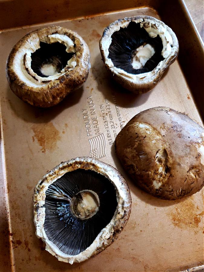 Portobello mushroom caps on a baking sheet