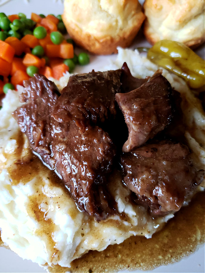 Mississippi Pot Roast with sides and gravy on a dinner plate
