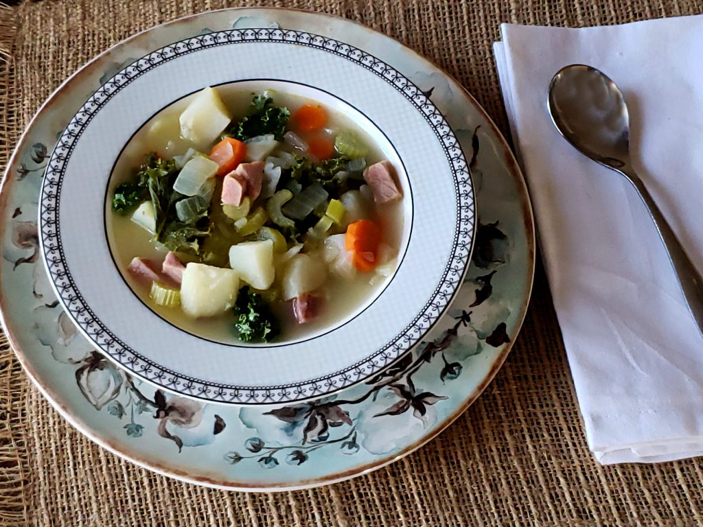 Blue bowl with cotton pattern with ham potato kale soup serving