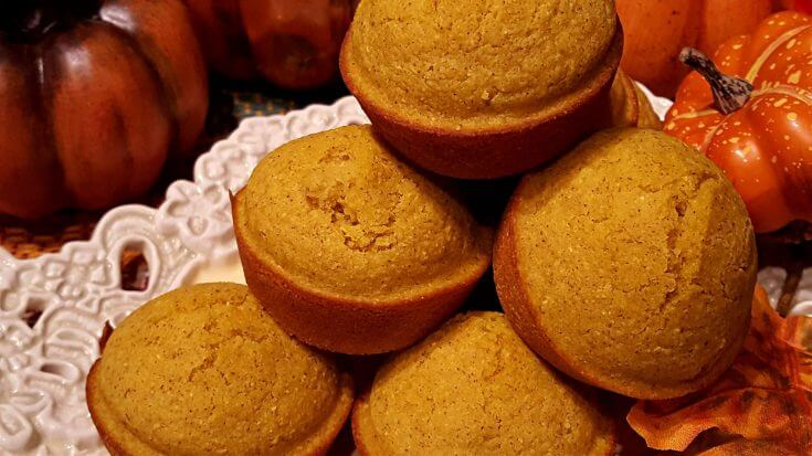Pumpkin Cornbread Muffins on a serving tray next to decorative pumpkins