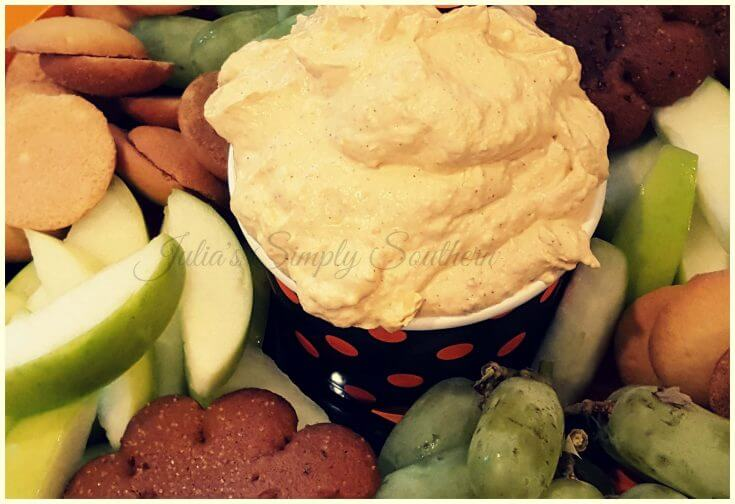 Pumpkin fluff dip on a platter with fruit and cookies