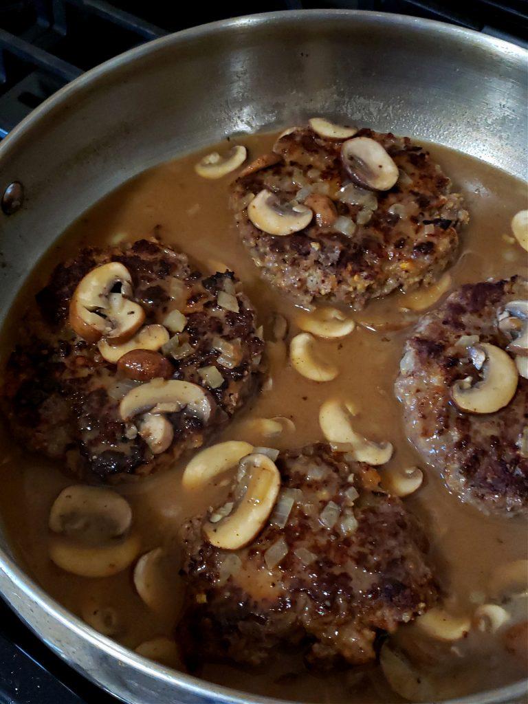 Salisbury Steaks in mushroom gravy simmering in a skillet