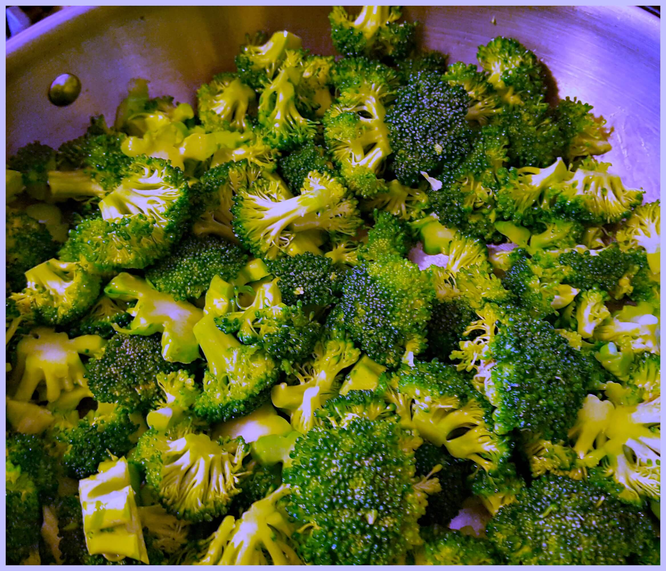 fresh broccoli cooking in a stainless skillet
