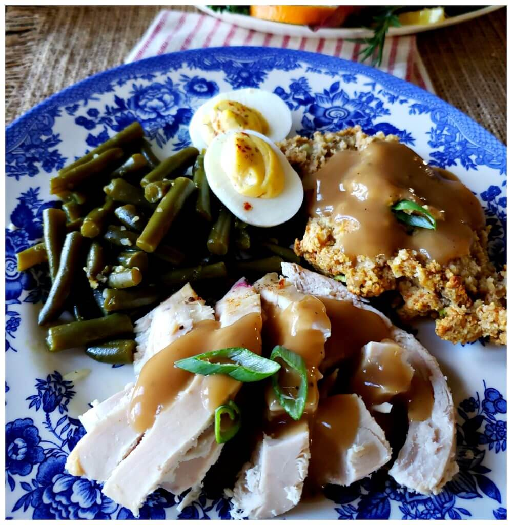 Plate with sliced turkey, stuffing, green beans, deviled eggs and gravy
