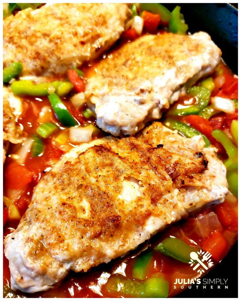 A bed of vegetables topped with pan fried pork chops