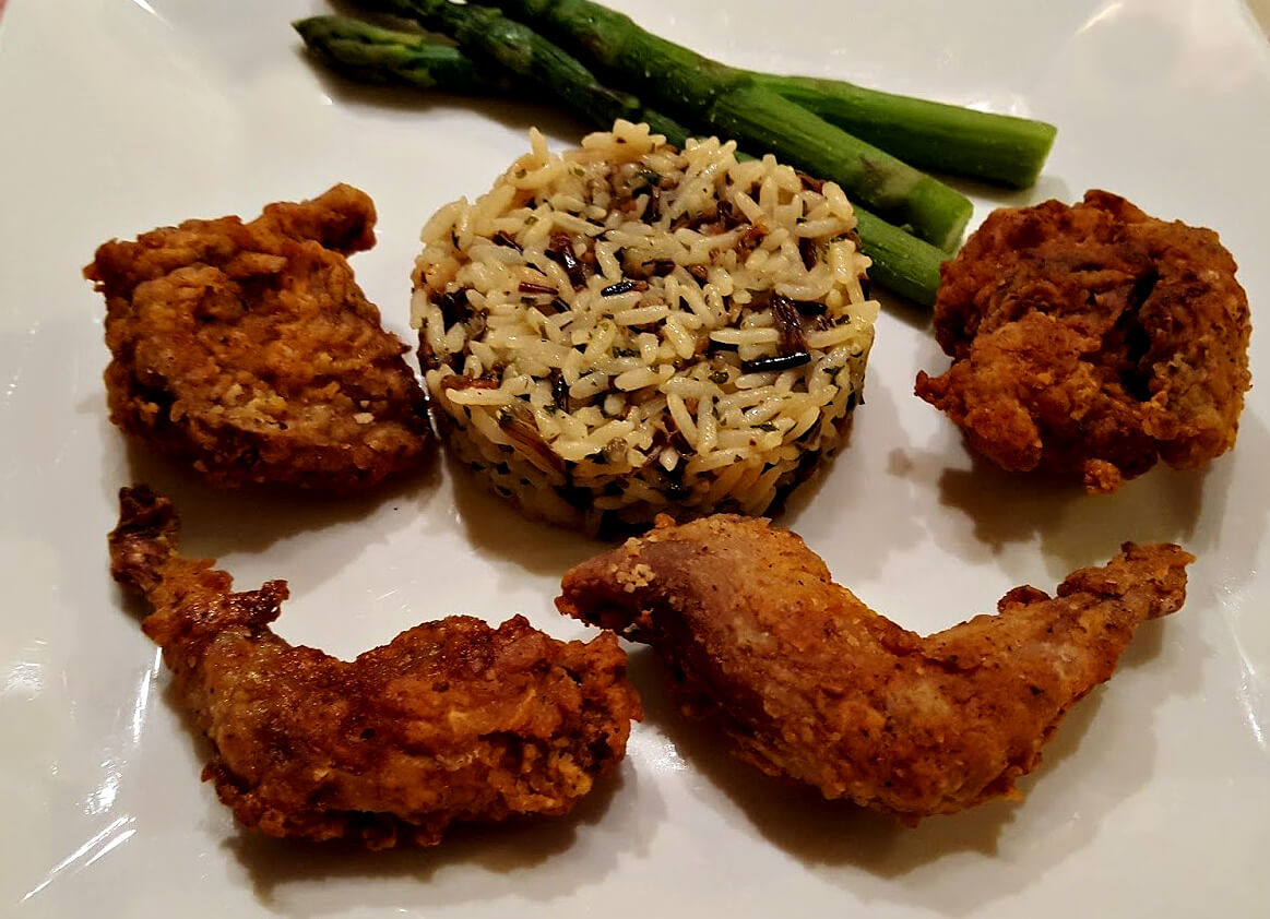 fried quail on a plate with wild rice and asparagus
