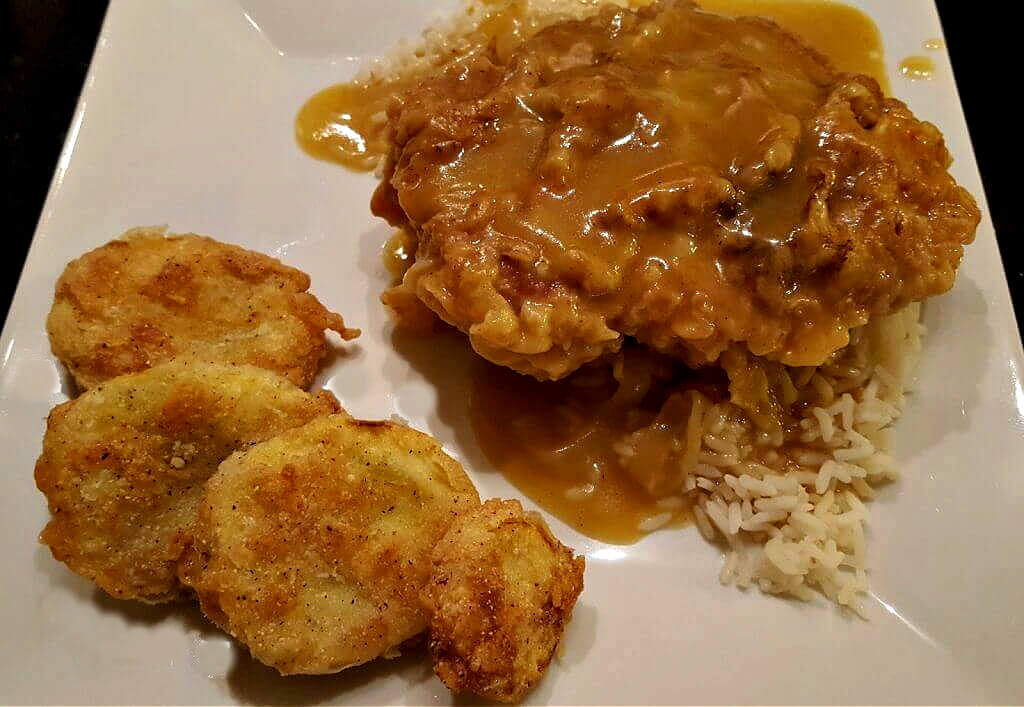 Smothered Pork Chops on a white plate with rice and fried yellow squash