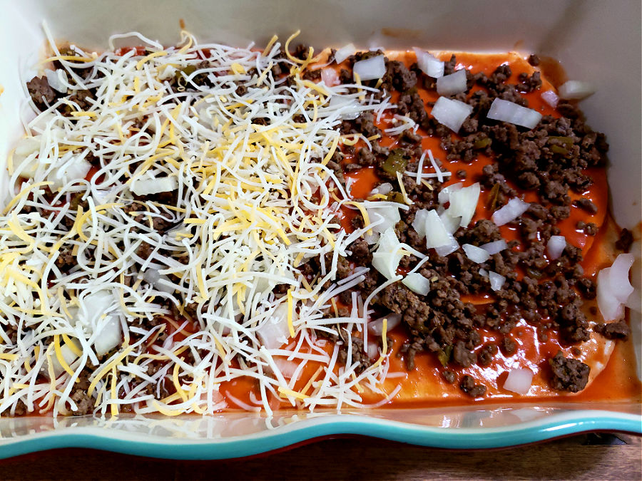 Layering tortillas, ground beef, onions and cheese into a casserole dish