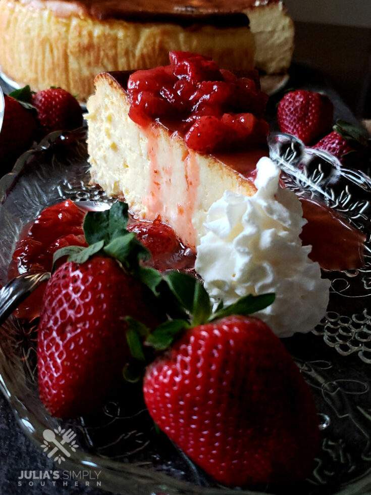 Strawberry topping recipe for cheesecake on a glass plate surrounded by fresh strawberries and whipped cream