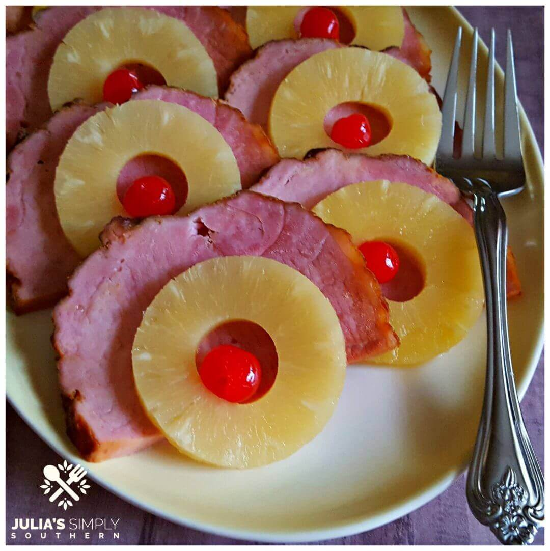 Crock Pot Holiday Ham - Pineapple Glazed slow cooker ham topped with pineapple rings and cherries on a yellow platter with a serving fork