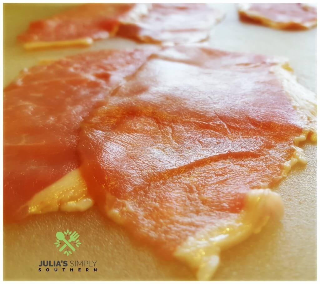 Thin pork cutlets on a cutting board to prepare pork cordon bleu