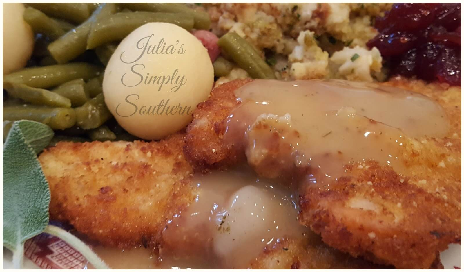 Breaded Turkey Breast Cutlets with gravy on a plate with green beans, stuffing and cranberry sauce