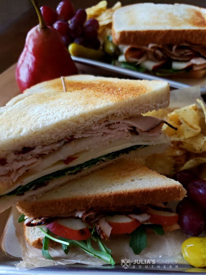 Turkey sandwiches on serving trays with sides